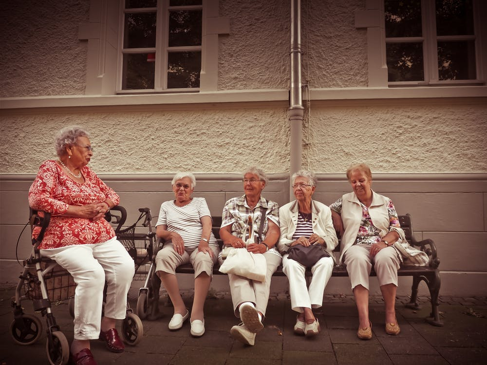 Old woman inquiring about nursing home costs to other senior citizens