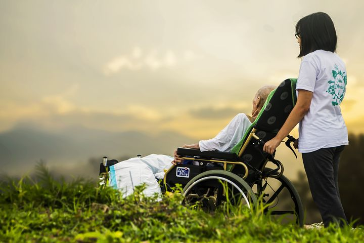 Young woman assisting an old man in the wheelchair